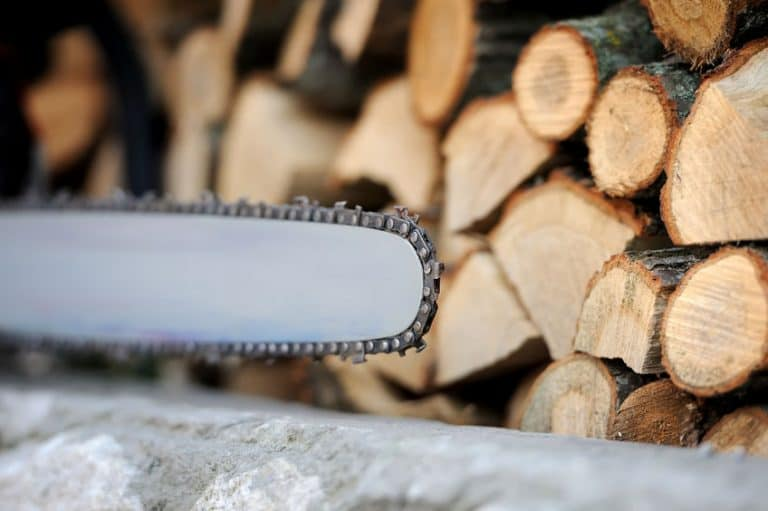 Motosierra con troncos de madera