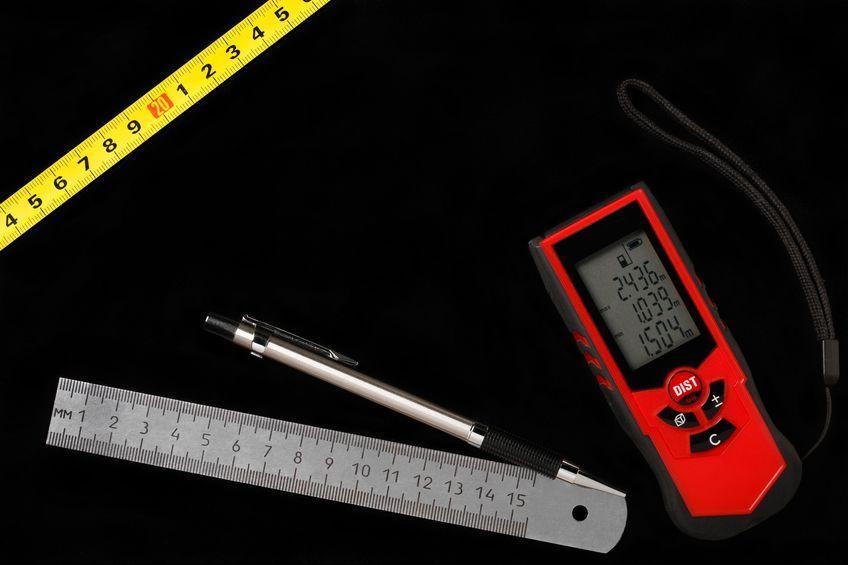 Cinta métrica, medidor de distancia láser y regla metálica con lápiz sobre fondo negro