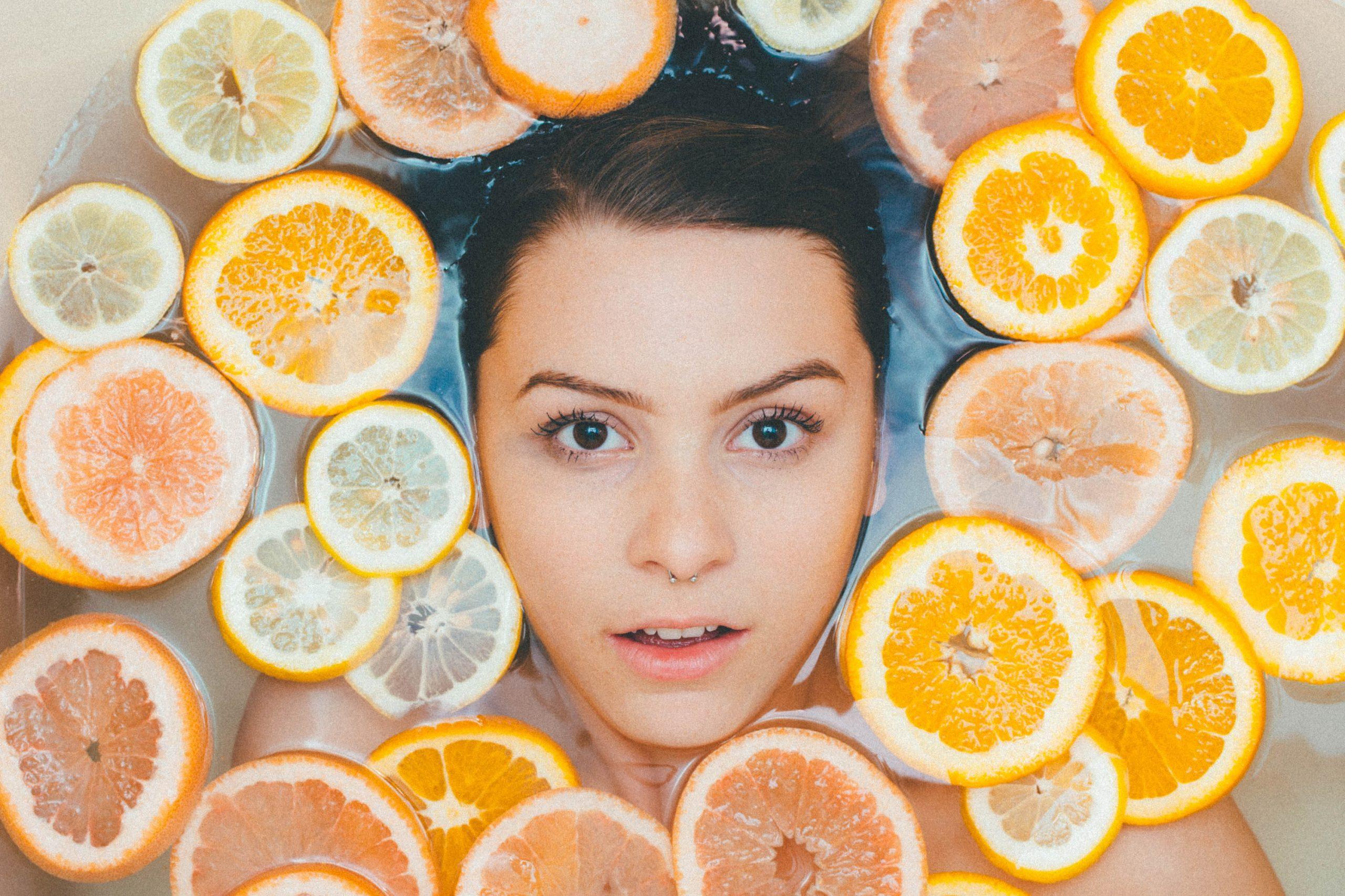 Mujer rodeada de rodajas de naranja