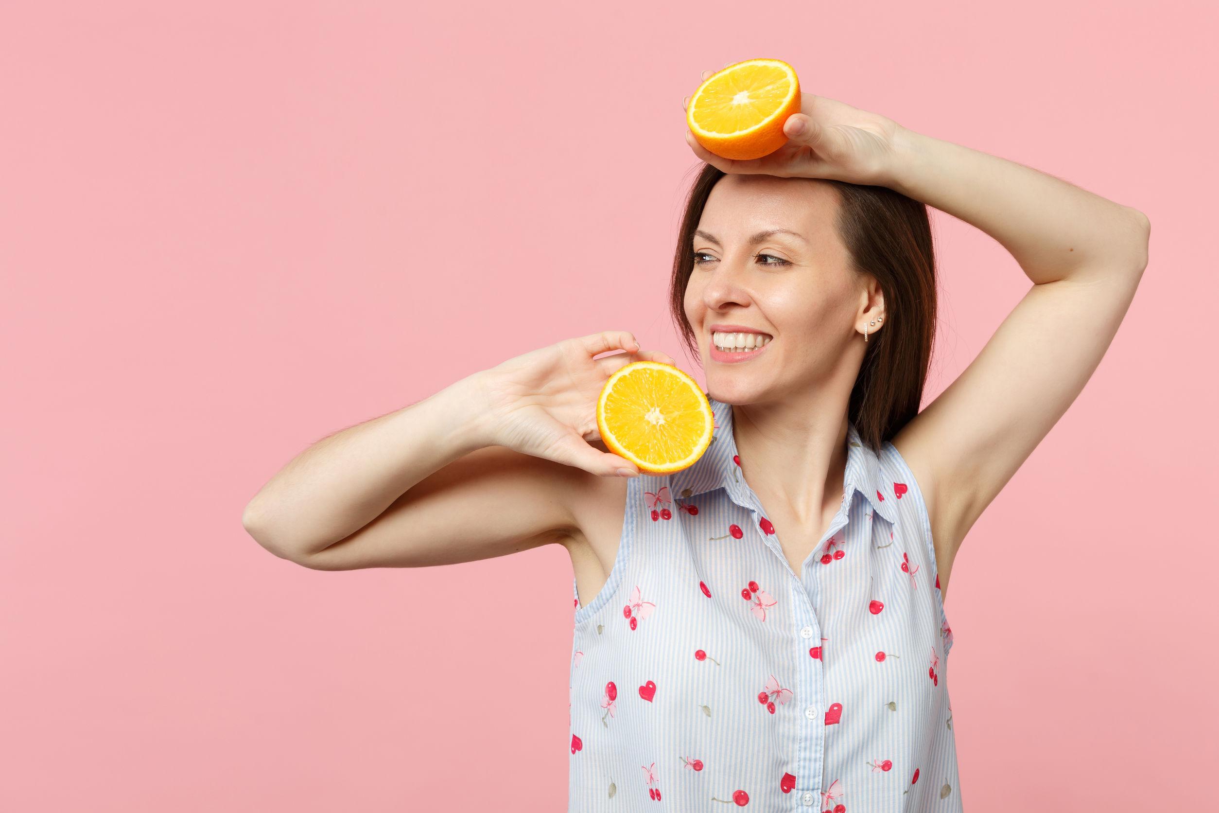 Sonriente a mujer joven en ropa de verano mirando a un lado sosteniendo dos mitades de fruta naranja madura fresca aislada sobre fondo rosa pastel.