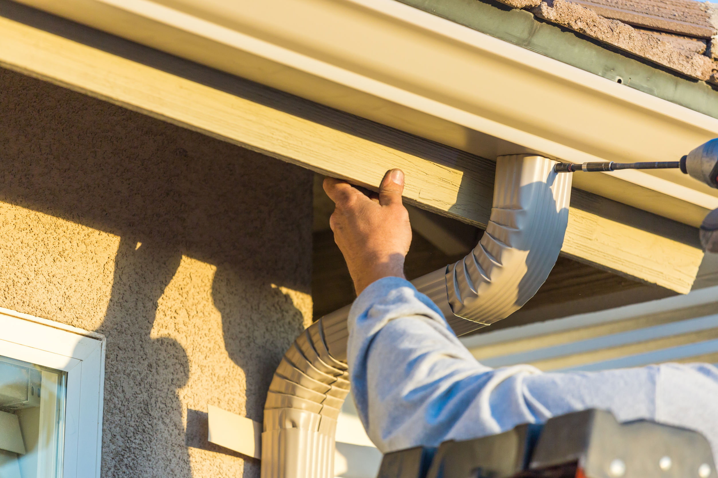 rabajador que fija el canalón de aluminio de la lluvia y abajo el canalón a la fascia de la casa.