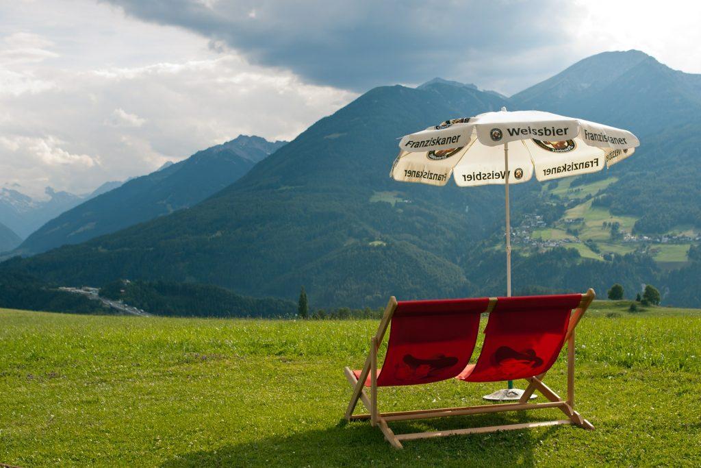 Tumbona al aire libre con sombrilla sobre césped