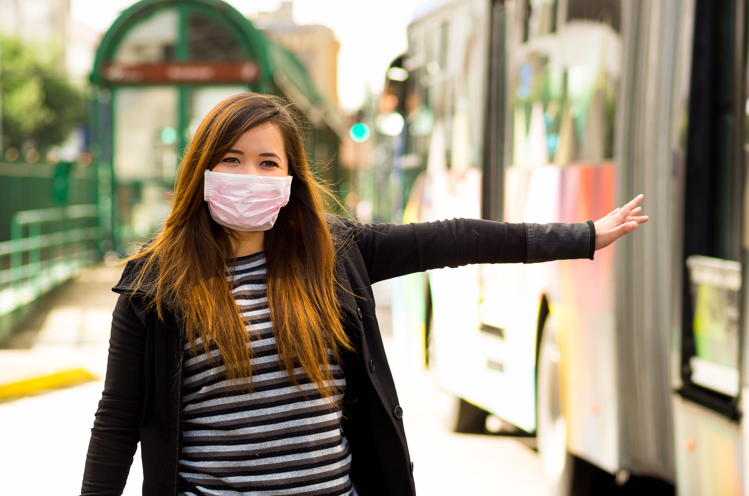 Feliz hermosa joven con máscara protectora en la calle de la ciudad con contaminación del aire, pidiendo un taxi con un autobús borroso detrás