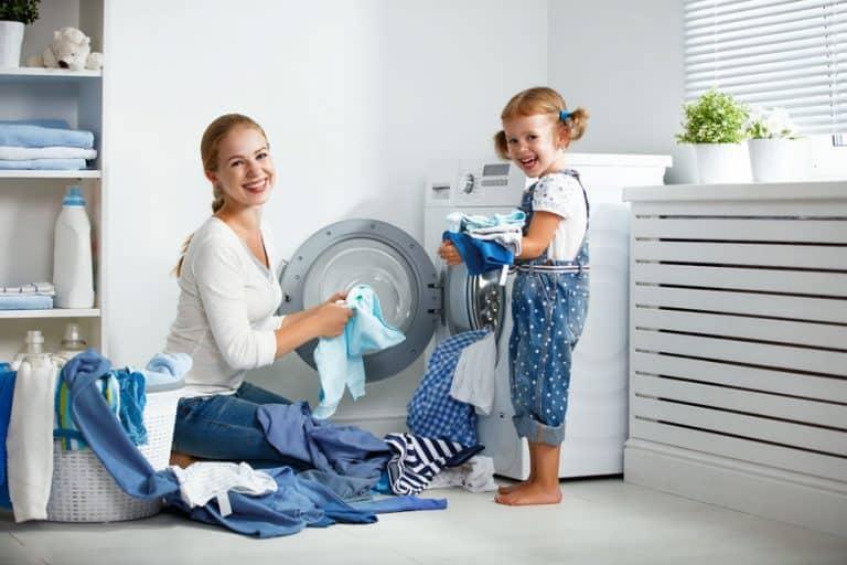 Una mujer y una niña poniendo una lavadora