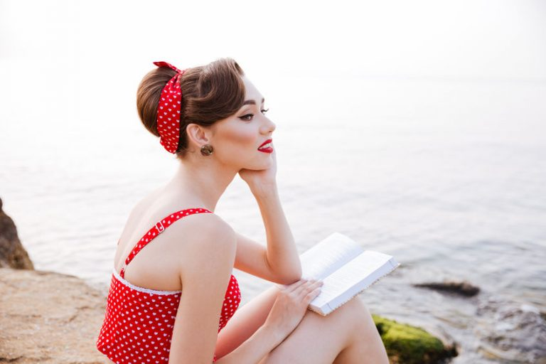 Mujer sentada en la playa con lazo para cabello