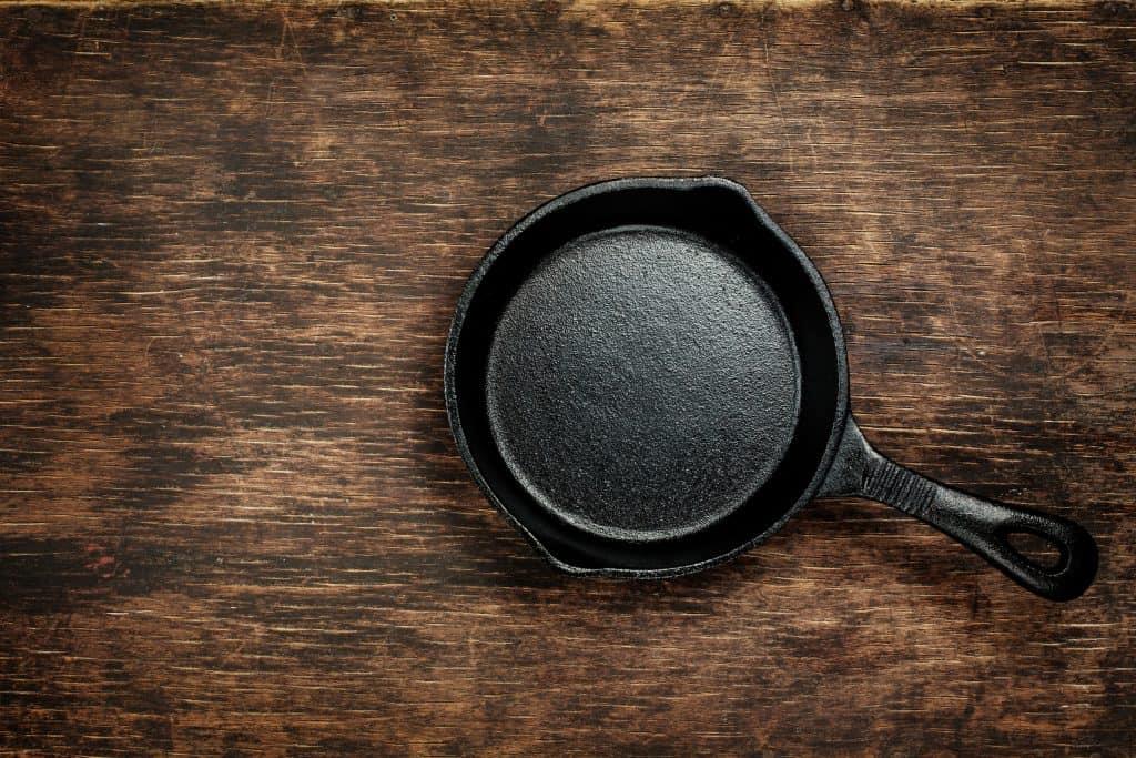 Imagem mostra uma frigideira de ferro limpa sobre uma bancada de madeira.
