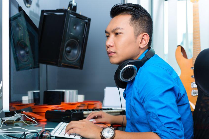 Músico asiático, productor o mezclador en estudio de sonido.