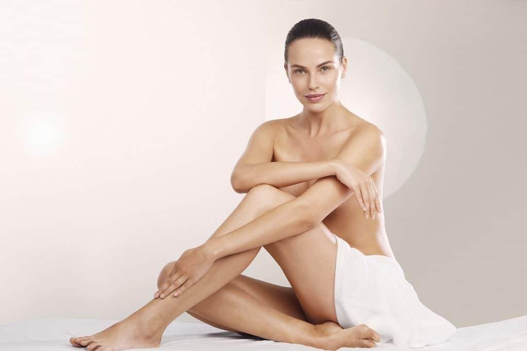 Foto de uma mulher sentada com uma das pernas apoiadas no chão e a outra dobrada. Ela está nua, apenas com uma toalha branca no colo, e cabelo preso em um coque.