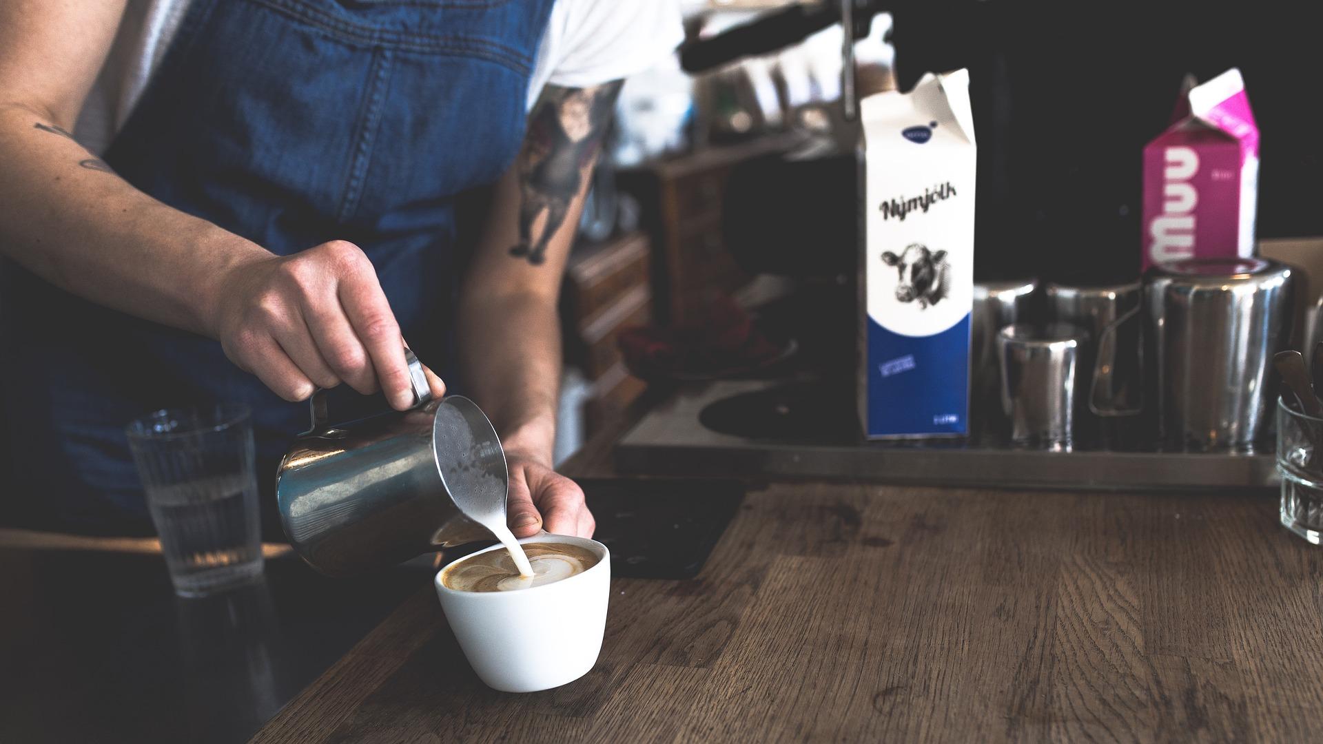 Barista colocando espuma de leite no café.