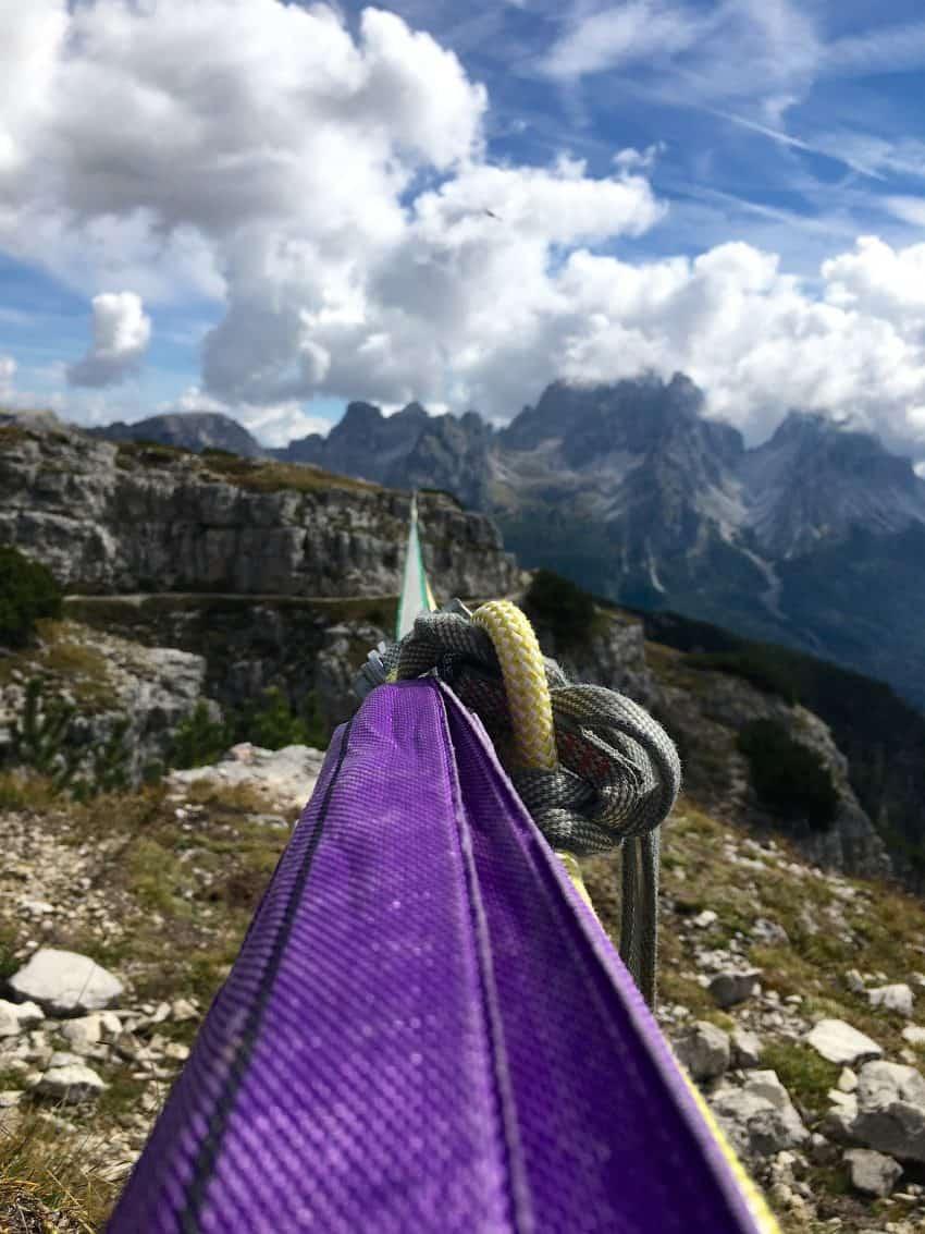 Imagem mostra uma fita de slackline muito comprida amarrada na extremidade de uma montanha, com a outra ponta se perdendo em meio às montanhas do fundo.