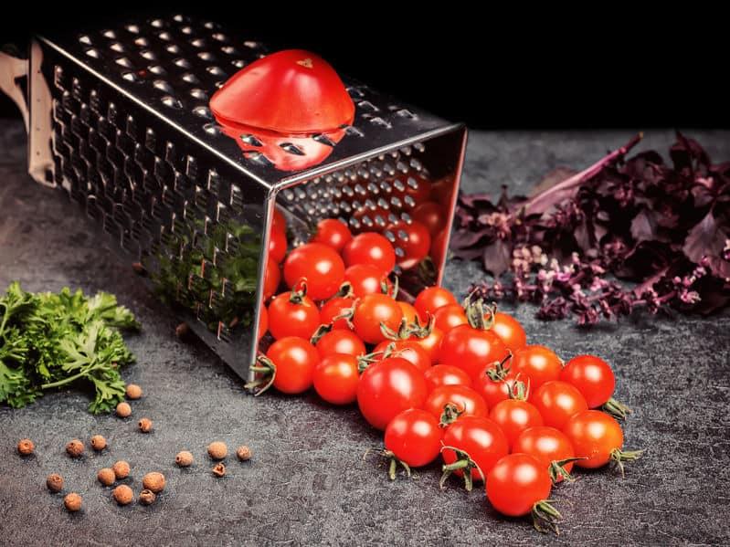 Imagem de tomates sobre cortador de legumes.