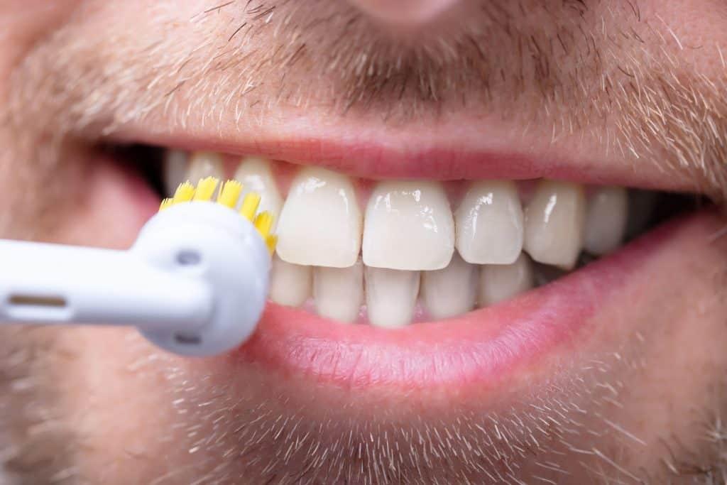Imagem de homem escovando os dentes com escova dental elétrica.