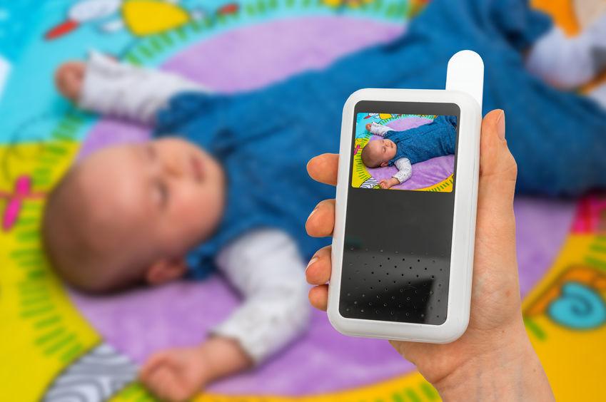 Mãos segurando monitor de babá eletrônica.