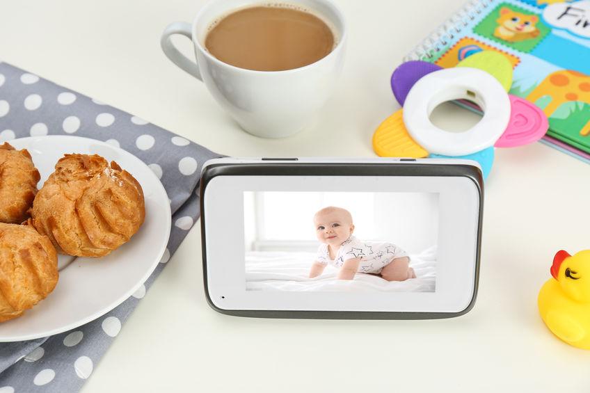 Unidade de monitoramento da babá eletrônica sobre a mesa ao lado de prato e xícara de café.