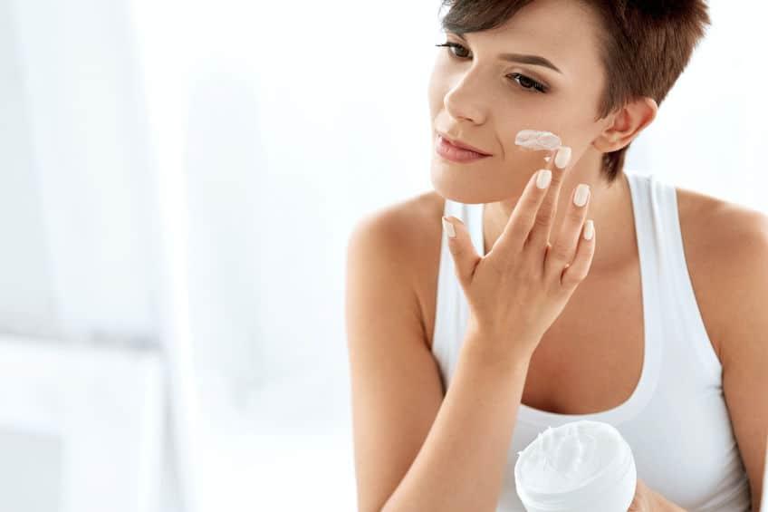 Mulher segurando pote de creme hidratante com uma mão e aplicando no rosto com a outra.
