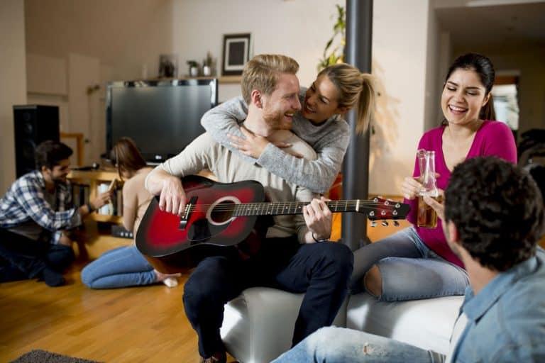 Un grupo de personas escuchando tocar la guitarra