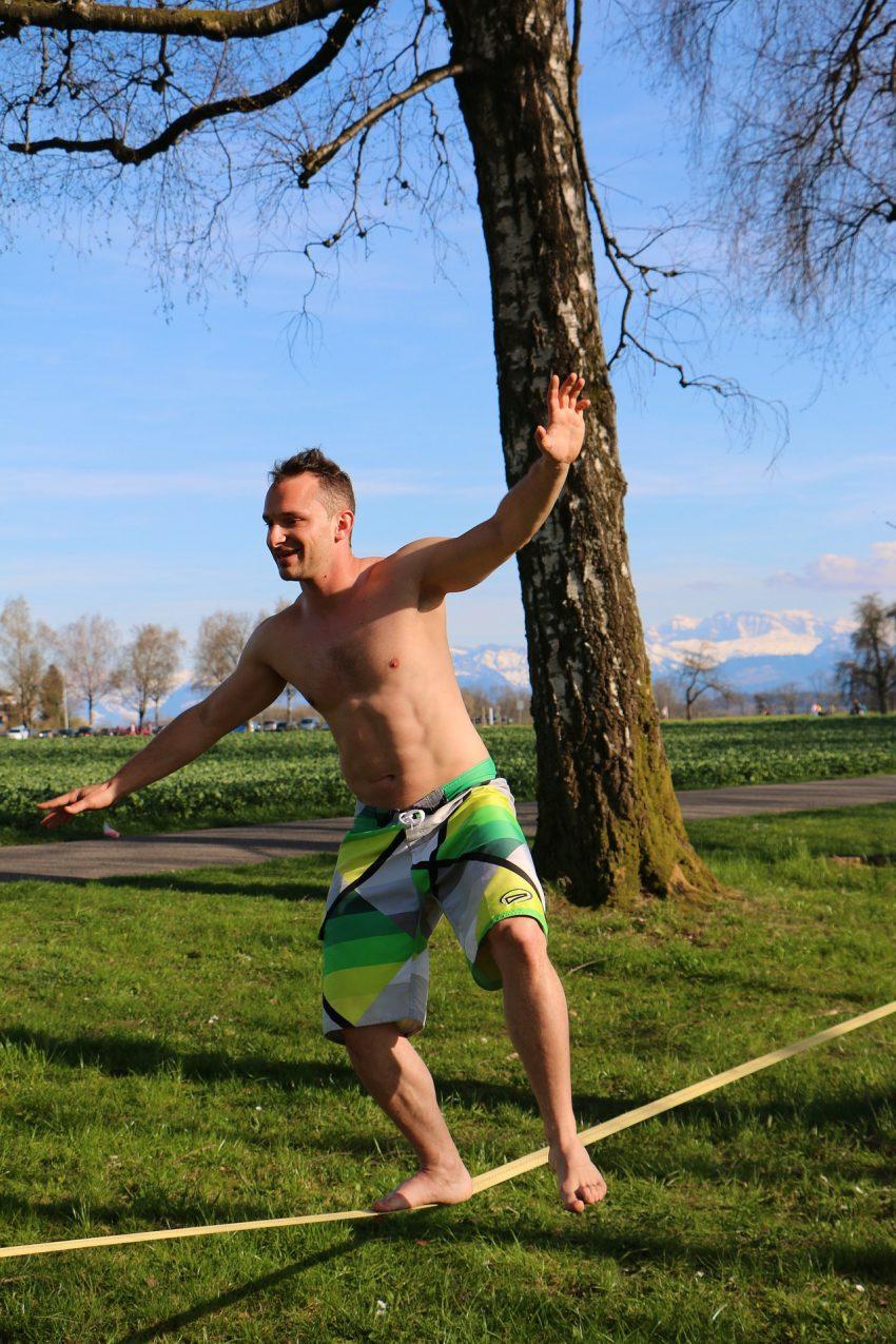 Imagem mostra um homem de bermuda se equilibrando numa fita de slackline em um parque.