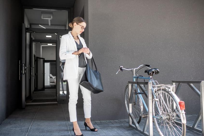 Mulher ao lado de bicicleta em suporte.