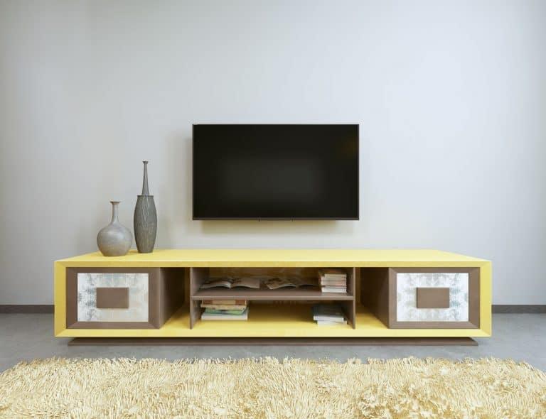 Na foto uma televisão instalada em uma parede em cima de um aparador.