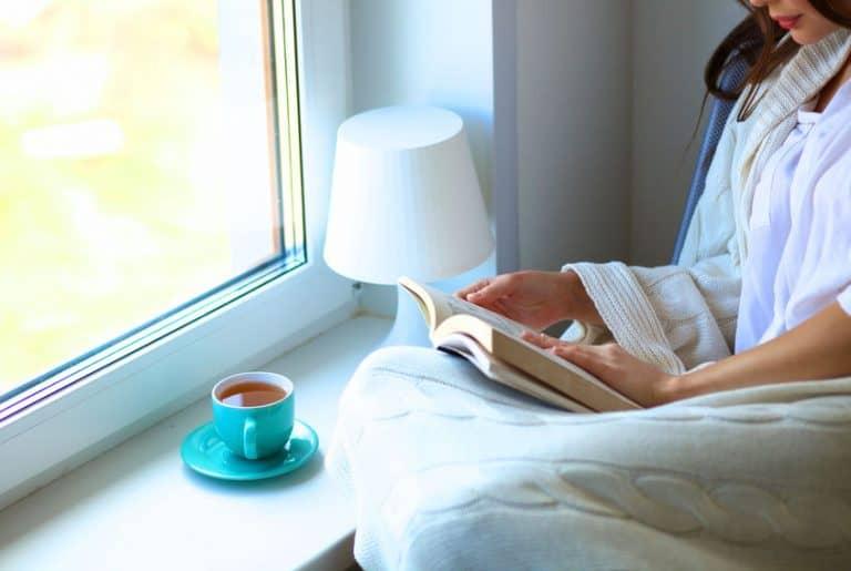 Mujer leyendo frente a la ventana
