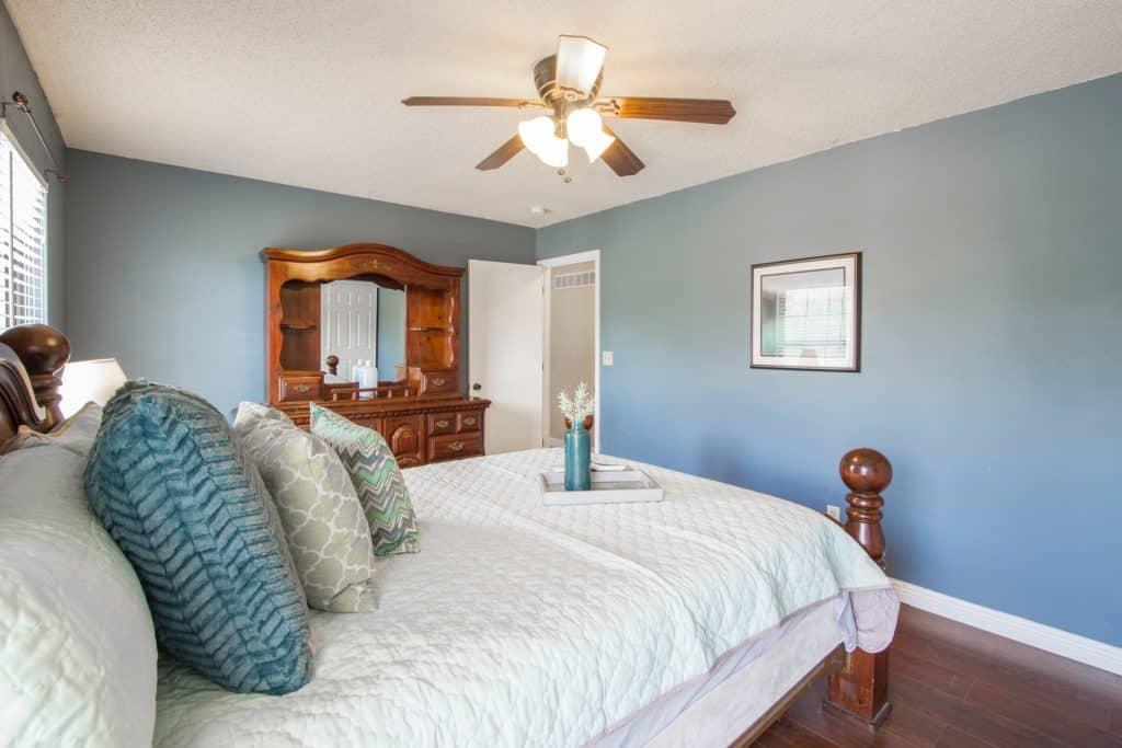 Imagem mostra um ventilador de teto em um quarto.