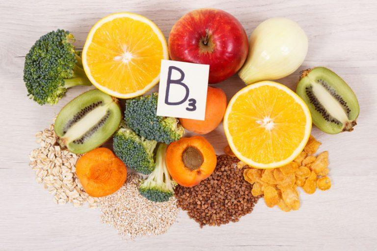 Alimentos como maçã, laranja, kiwi, brócolis e uma placa com B3 escrito.