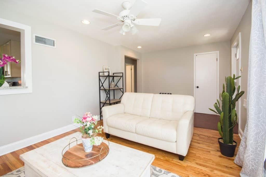 Imagem mostra uma sala de estar com um ventilador de teto compondo decoração clean.