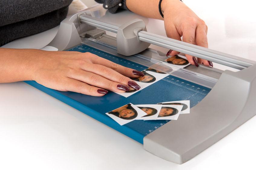 Imagem mostra uma pessoa cortando pequenas fotografias em uma guilhotina.