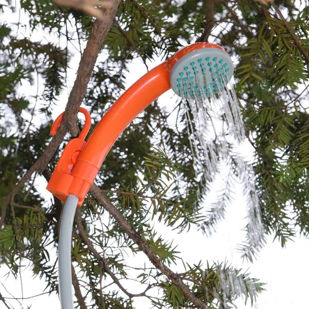 Chuveiro portátil alaranjado ligado pendurado em uma árvore.