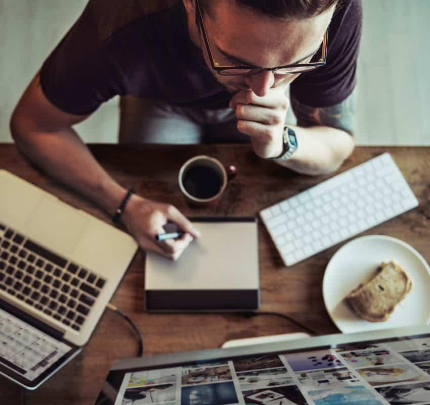 Homem sentado em frente ao computador usando mesa gráfica.