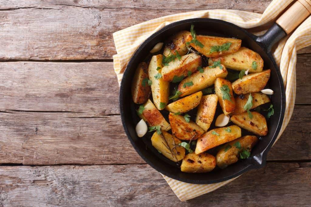 Frigideira de ferro com batatas dentro em cima de um pano de prato.