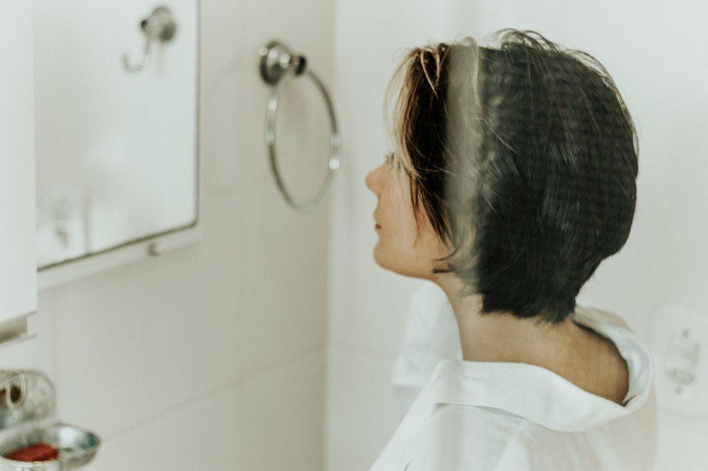 Moça se olha em espelho ao lado de toalheiro de argola