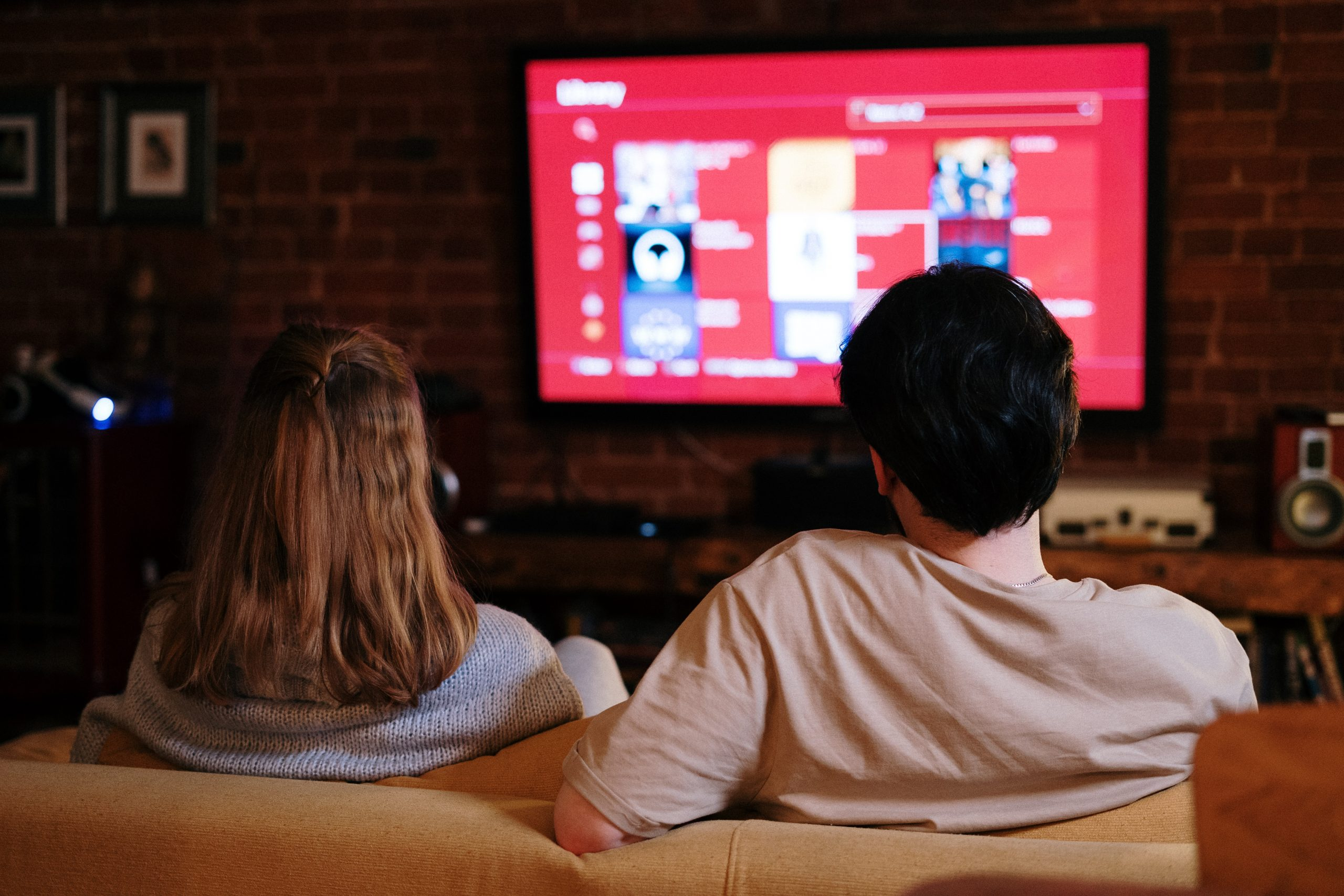 casal no sofá da sala com TV 75 polegadas ligada ao fundo