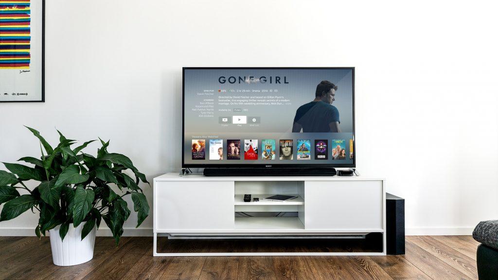 Na foto uma televisão ligada em uma sala de estar.