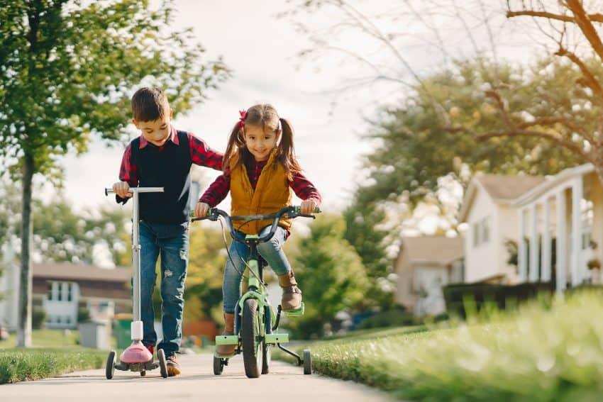 Na calçada de bairro familiar um menino anda de patinete ao lado de uma menina em uma bicicleta com rodinhas.