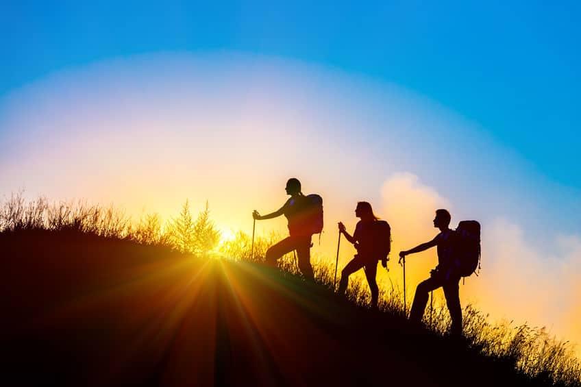 silhueta de três pessoas fazendo uma trilha