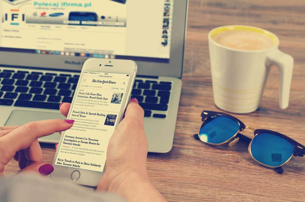 Mãos teclando no celular, com notebook e óculos Ray Ban.