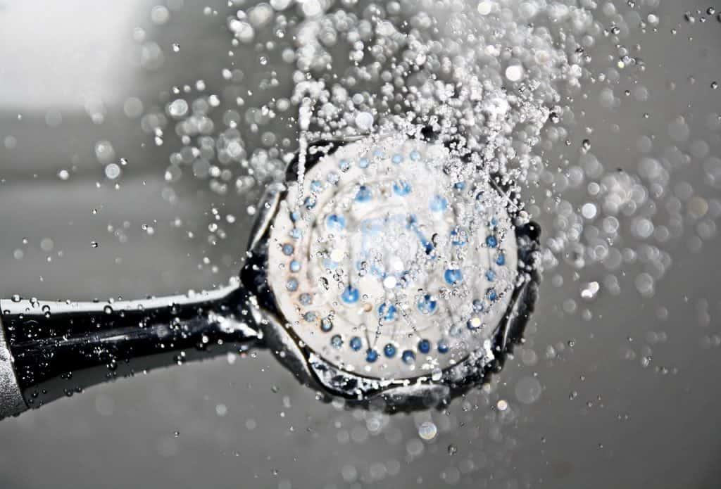Na foto o bocal de um chuveiro com água saindo.