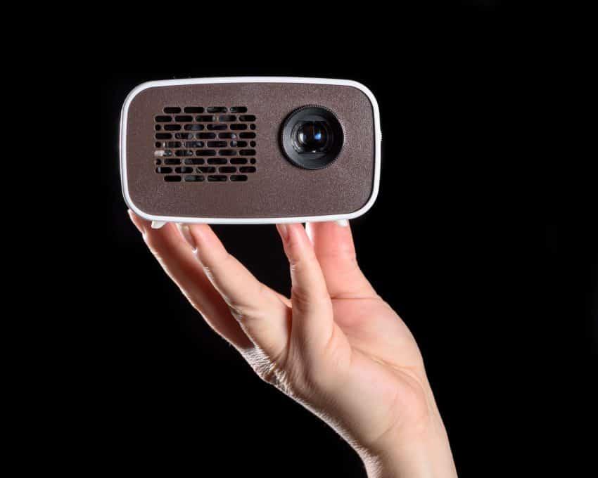 Imagem que mostra um mini projetor na mão de uma pessoa.