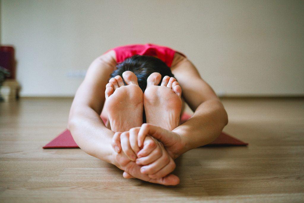 mulher sentada em um tapete de yoga fazendo posição difícil