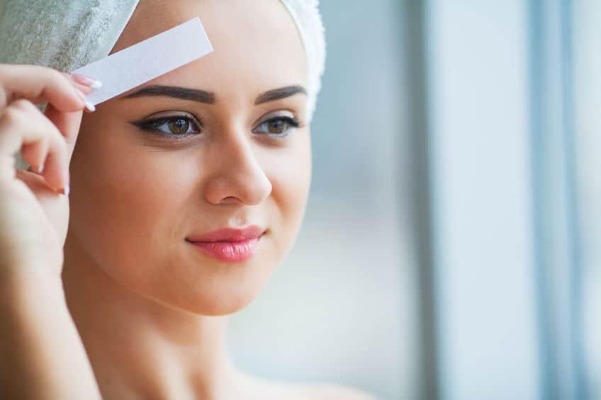 Mulher com toalha na cabeça segurando uma folha depilatória perto da sobrancelha.