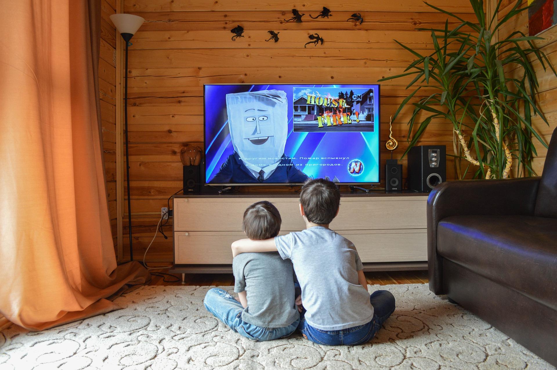 Imagem mostra duas crianças sentadas no chão assistindo a uma grande televisão