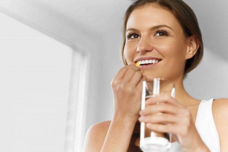 Mulher ingerindo suplemento com copo de água.