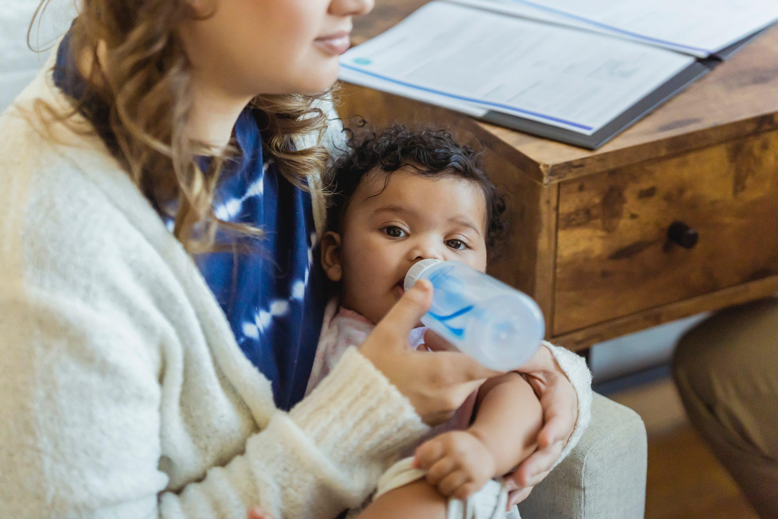 Mulher dando mamadeira para bebê
