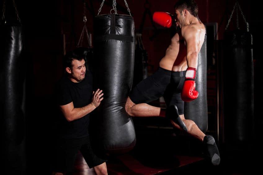 Imagem de um homem dando um chute em saco de pancada enquanto outro homem apoia o saco de pancada.