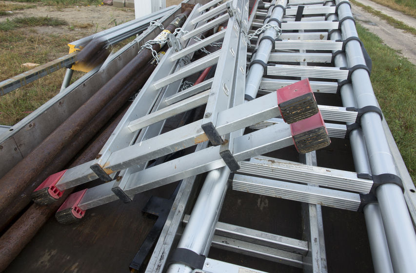 Várias escadas expansíveis de alumínio colocadas no chão