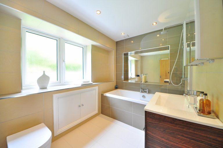 Banheiro em estilo moderno com tons de areia e madeira com duas saboneteiras para sabonete liquido sobre bancada da pia