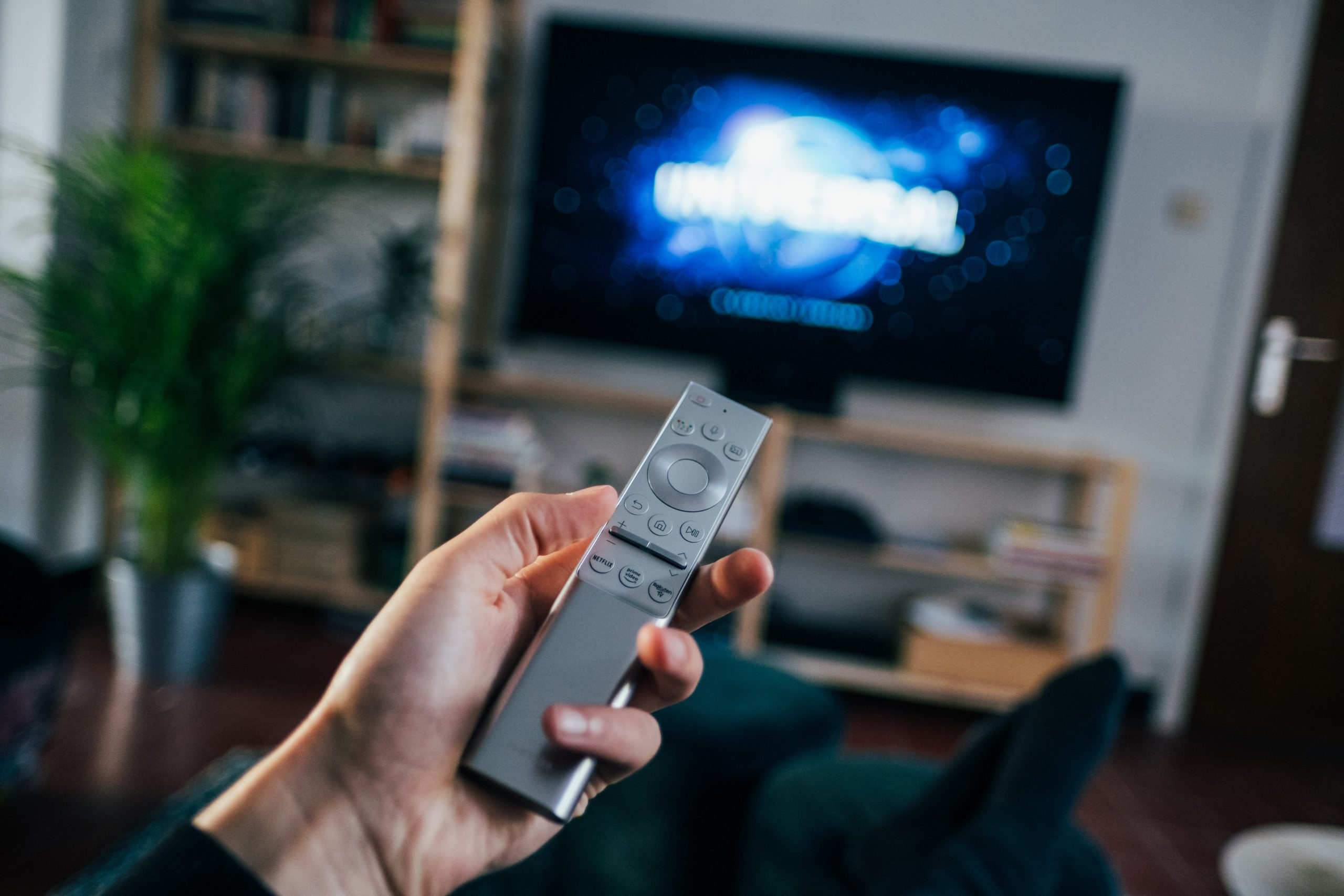 Persona sosteniendo control de Samsung con smart TV de fondo