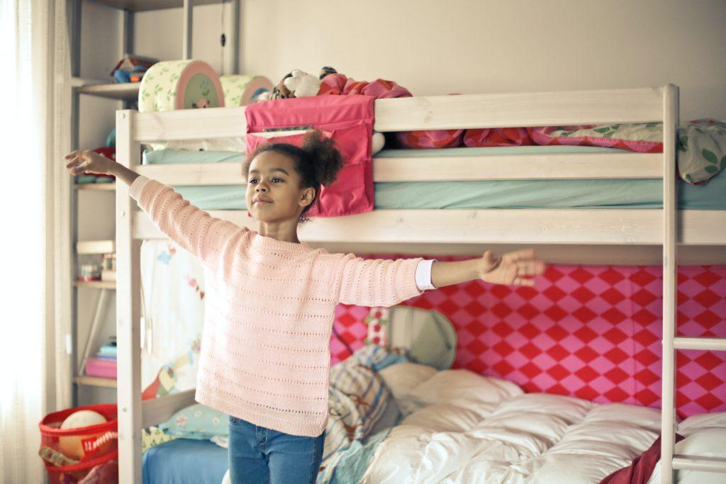 Niña con brazos extendidos frente a camarote infantil