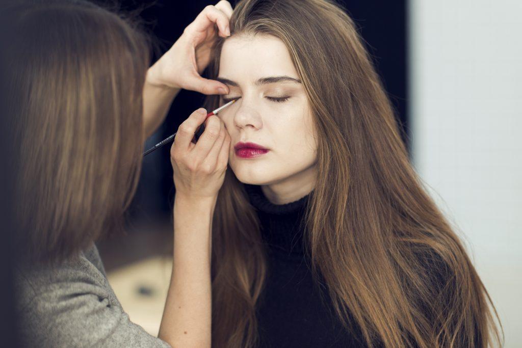 Maquiadora aplica delineador em uma moça com pincel para delineado